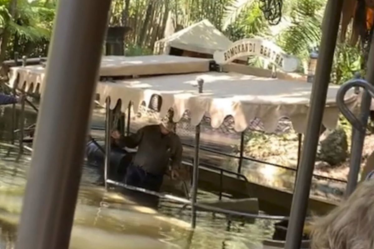 A person stands knee-deep in water aboard a Jungle Cruise boat after the vessel took on water, Thursday, Feb. 27, 2020, at Walt Disney World in Orlando, Fla.
