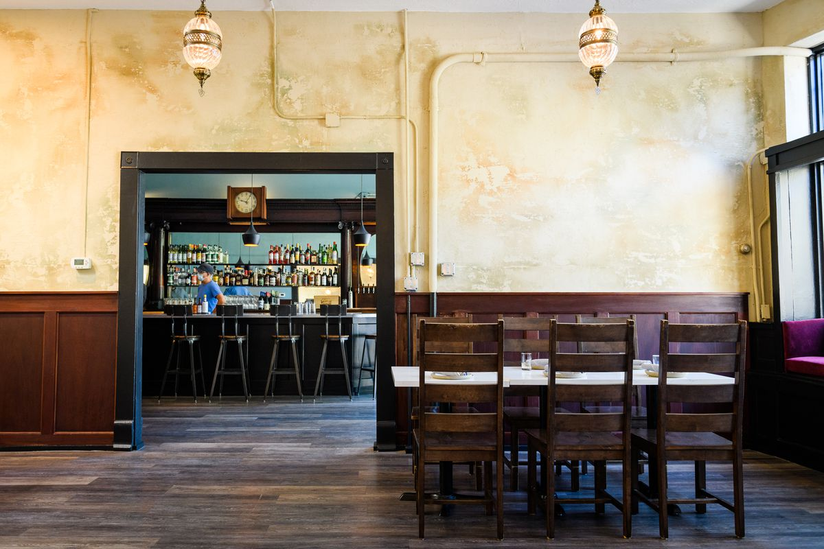 The yellow-tinted walls of Yalla are lined with wooden paneling, more polished than the rustic wooden floors. In the dining room, tall wooden chairs circle white tables.