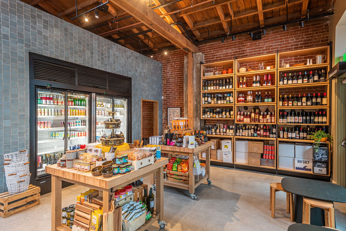 Wooden butcher block tables show snacks, while a cooler and back wall showcase lots of wine.