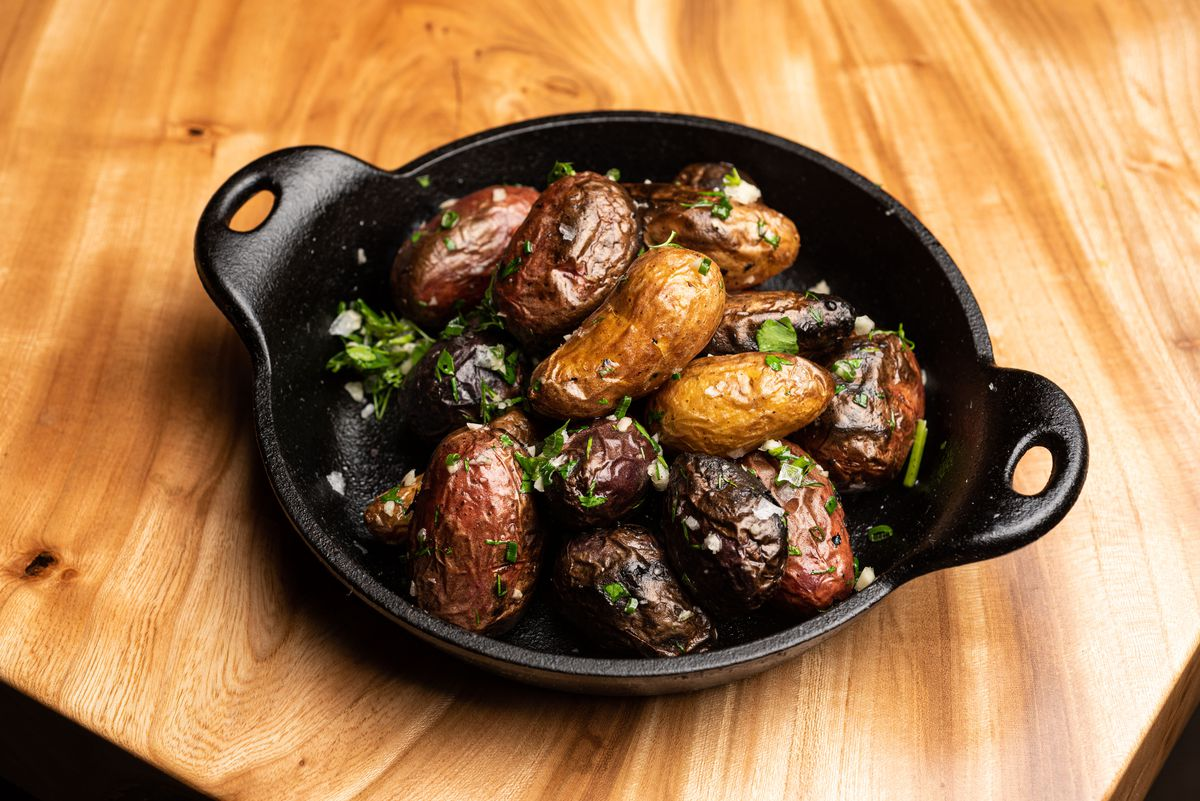 A metal pan of roasted and salted potatoes.