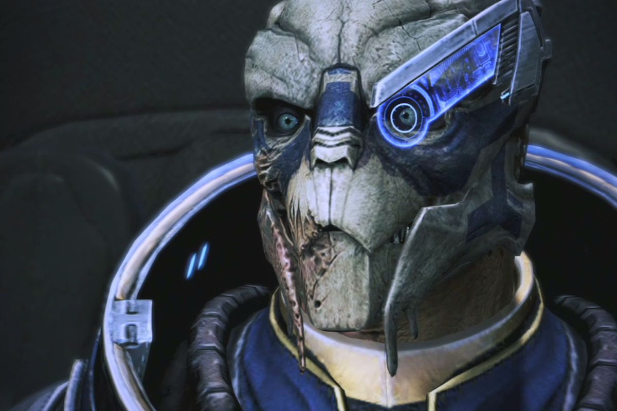 Garrus Vakarian looks at the camera. He's a lizard-looking alien, with a blue visor over one eye, and scars up the side of his face.