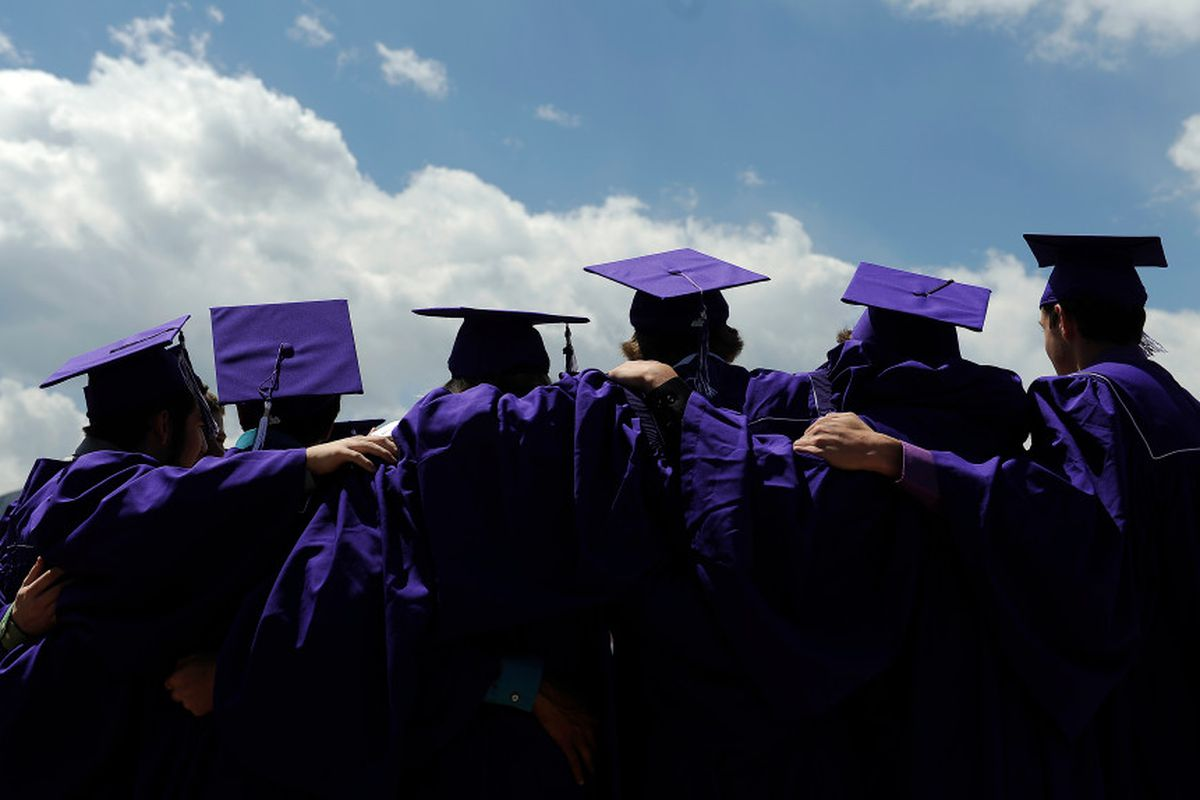 The backs of six students in purple caps and gowns in a line with their arms around each others' shoulders.