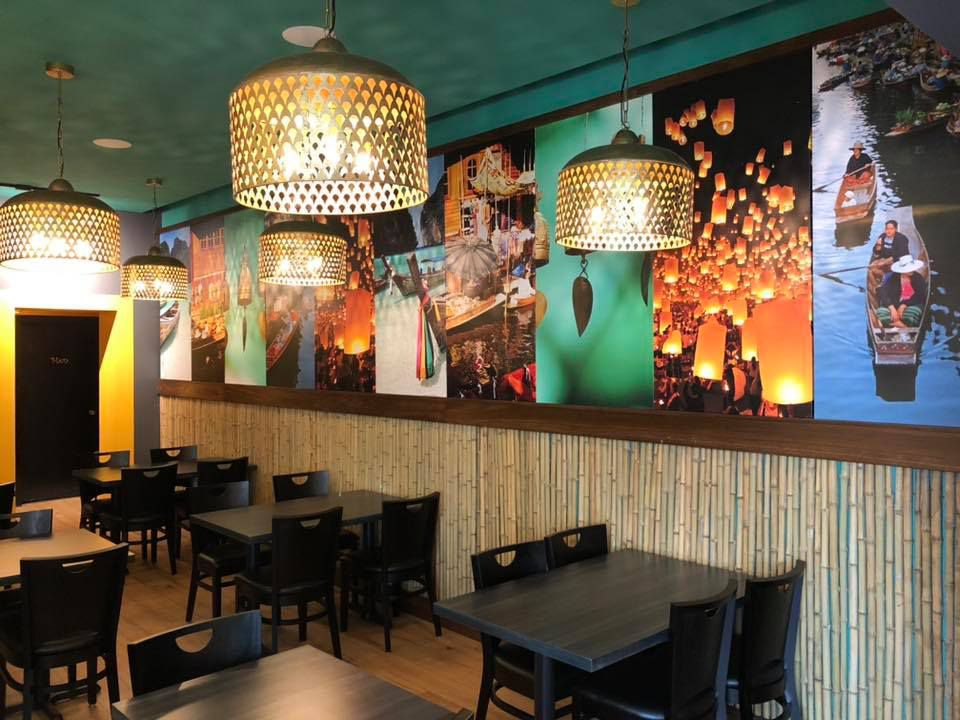 A restaurant interior with decorative cane pendant lights and images of Thailand on the walls
