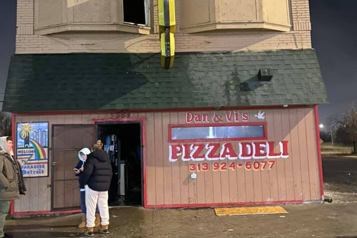 People gather outside a fire-damaged Dan and Vi's in early December 2020.