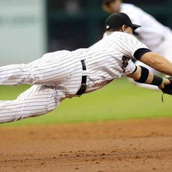 Houston Astros third baseman Chris Johnson dives for a base hit by Atlanta Braves' Dan Uggla during the second inning of a baseball game on Wednesday, April 11, 2012, in Houston.