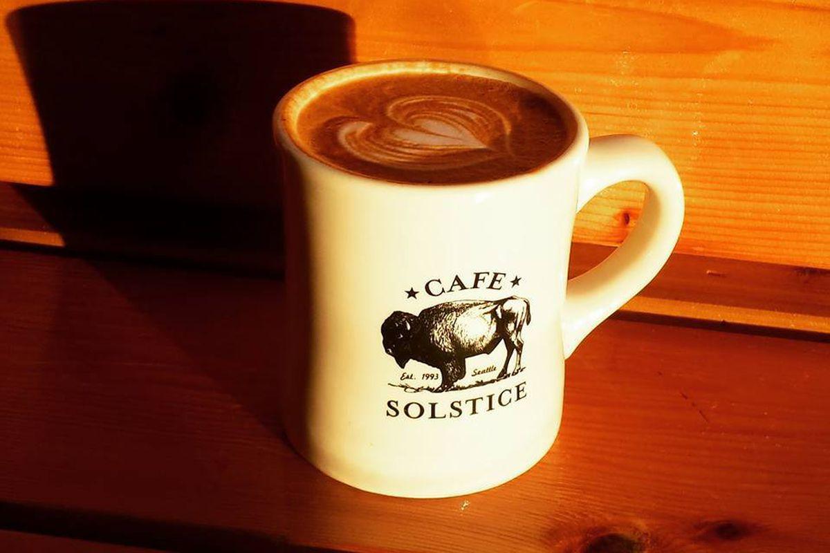 A closeup shot of a coffee mug with Cafe Solstice's logo.