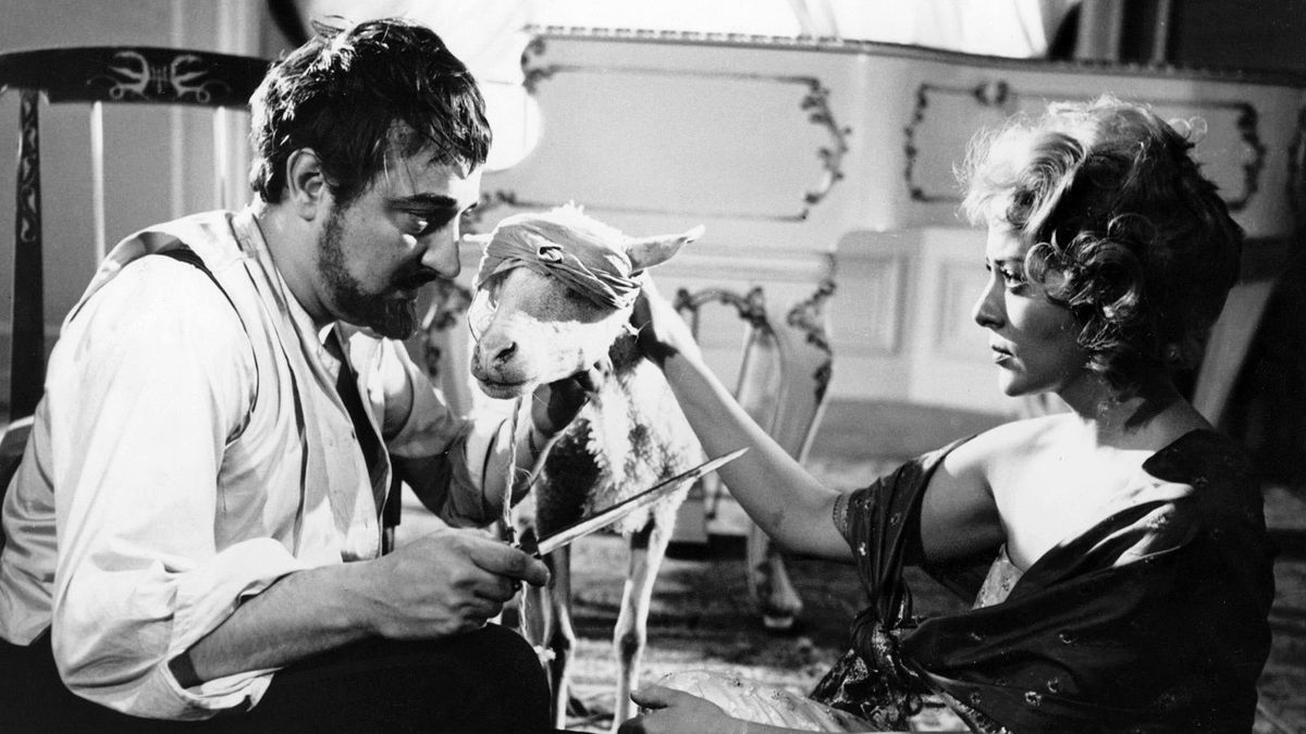 A man with a blindfolded lamb brandishes a kife towards a woman staring intensely at him in The Exterminating Angel.
