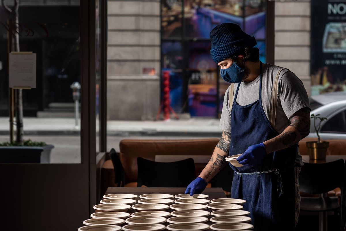 Man wearing face mask lines up disposable bowls on a table.