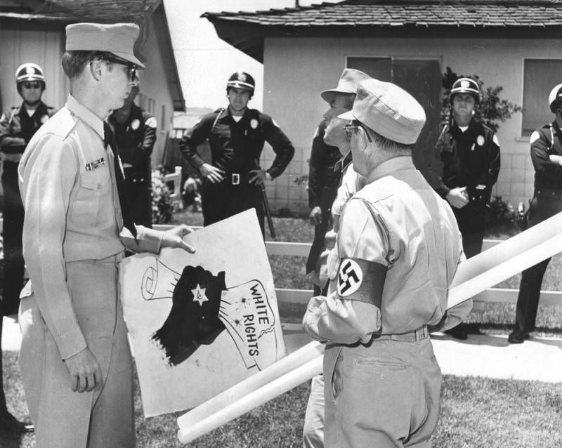 """White men wearing military uniforms and armbands with the swastika symbol hold a sign that says """"White rights."""" Police officers are visible in the background."""