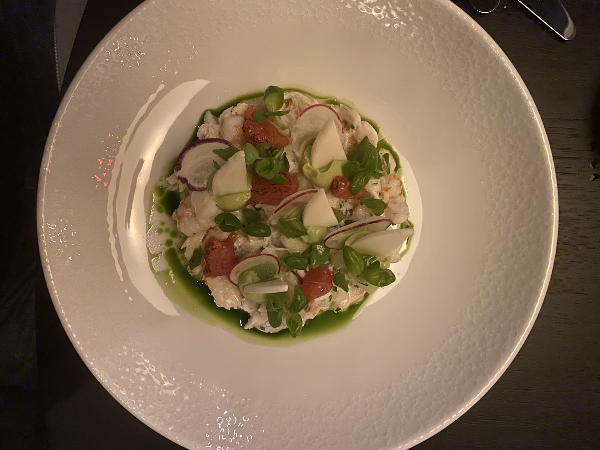 Pieces of crab, shrimp, hearts of palm, radish, and basil on a white plate