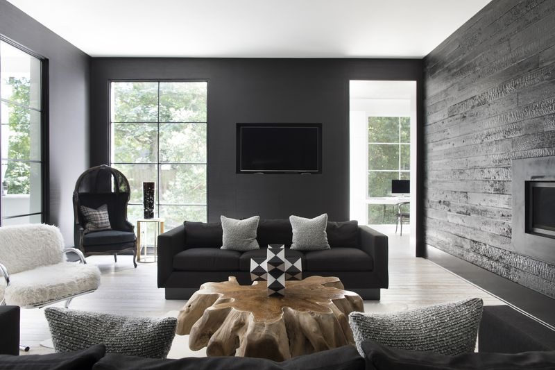 A dark gray sofa with a low back and two light gray cushions sits in the middle of a mostly monochromatic room.