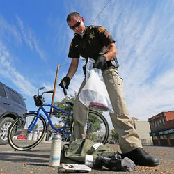 Utah Highway Patrol Sgt. Randy Riches picks up a gun and other items taken off a homeless man who was arrested during Operation Rio Grande in Salt Lake City on Monday, Aug. 14, 2017. Lawmakers say the three-phase plan will last two years and attempt to curb crime surrounding the Road Home shelter, help those faced with addiction and homelessness, and provide training and employment to those striving to improve their lives.