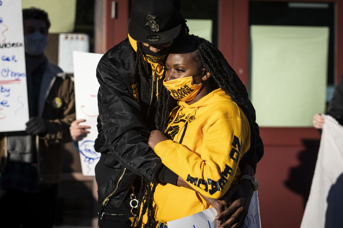 Shanece Williams hugs her son's father during a press conference about allegations that the 4-year-old boy was abused by security at John T. McCutcheon Elementary School in Uptown, Tuesday afternoon, Nov. 17, 2020.