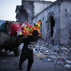 In this photo taken July 1, 2010, a man pulls a cart filled with merchandise in downtown Port Au Prince.