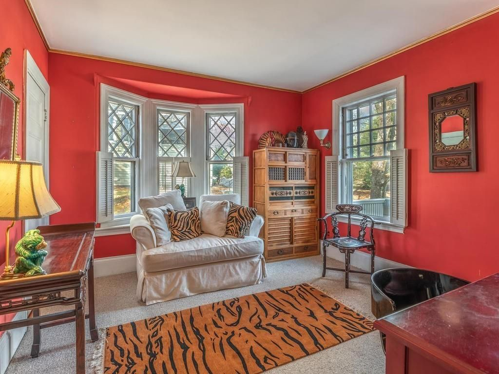A sitting room with bright red walls and a tiger-print rug.