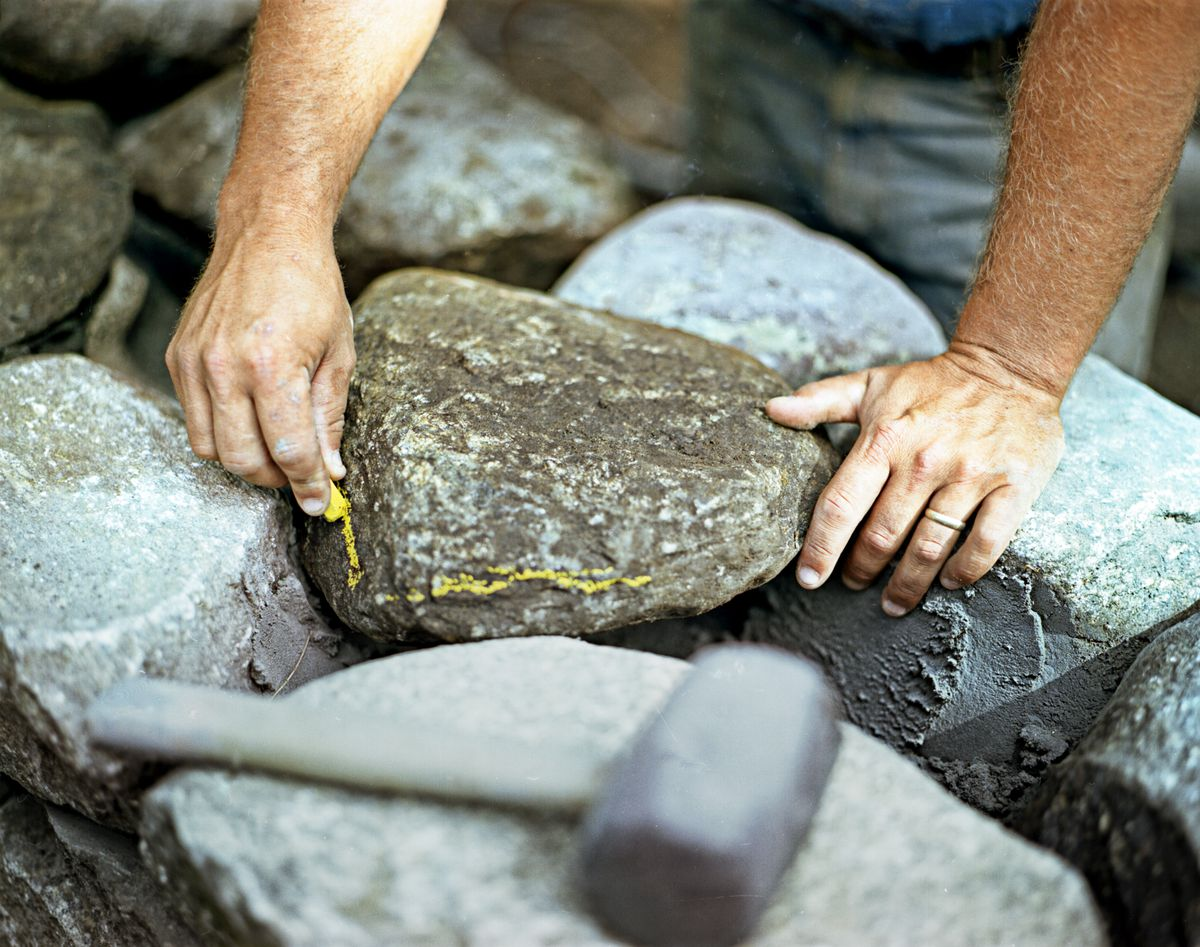 Man Marks Stone With Wax Pencil To Cut