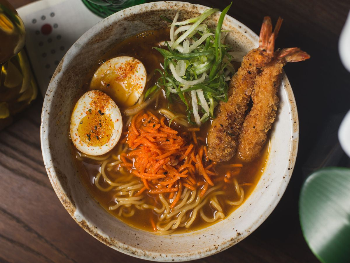 From above, a stone bowl of ramen in broth with boiled eggs, scallions, carrots, and shrimp tempura
