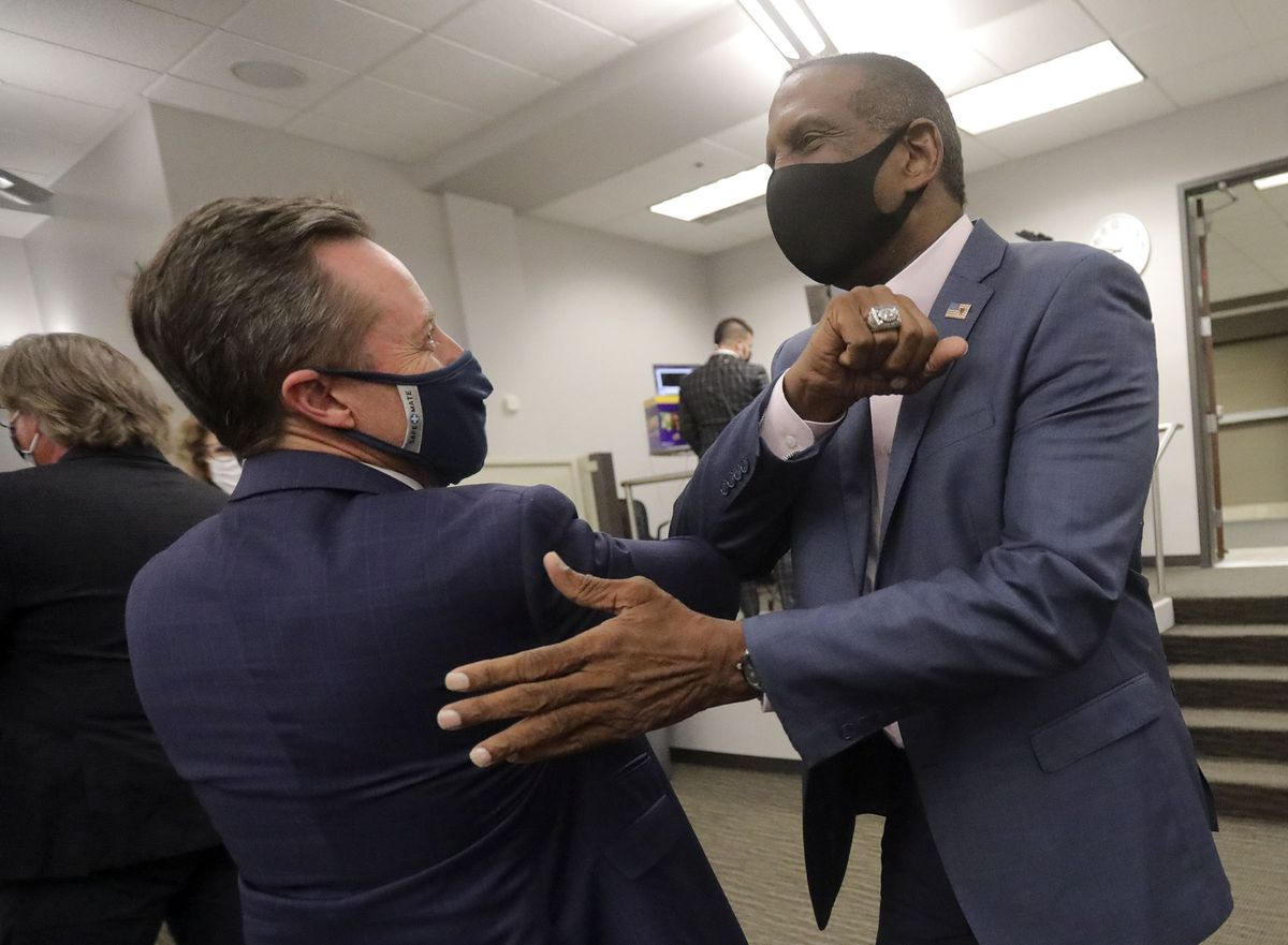 Derek Brown, Utah Republican Party chairman, elbow bumps 4th Congressional District candidate Burgess Owens, who is running against Rep. Ben McAdams, D-Utah, at a Republican election night event at the Utah Association of Realtors building in Sandy on Tuesday, Nov. 3, 2020.
