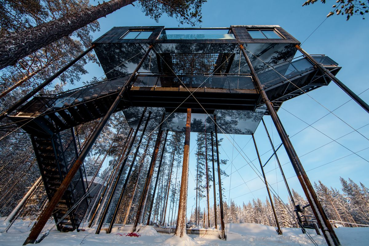 Bottom-up view of dark cabin perched on thin columns amid pine trees in a snow-covered forest.