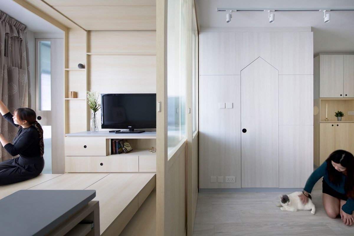 A woman sits next to a cat in a room with white cabinetry and a mirror.