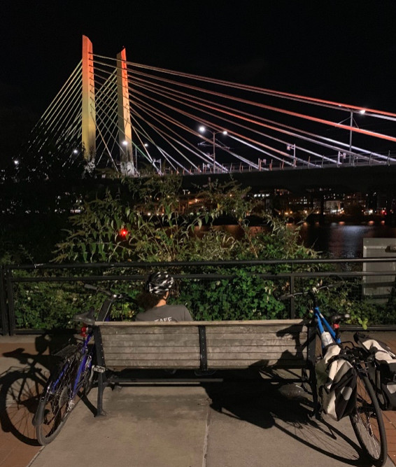 The spans of a large bridge are illuminated in orange and yellow against a black sky, while two people sit on a bench in the foreground with their bicycles.