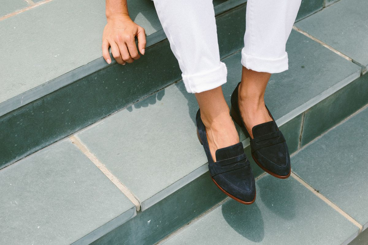 A woman shown sitting on green marble steps, shown from the waist down, wearing navy loafers and white jeans