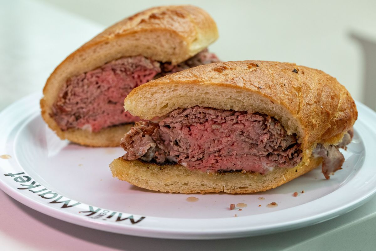 A photo fo the French 75 French Dip sandwich consisting of several layers of sliced prime rib on a hoagie roll