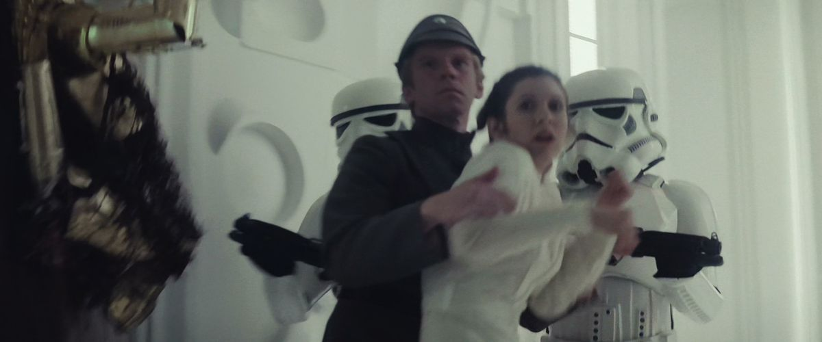 still frame from the Empire Strikes Back: Two Stormtroopers and an Imperial officer shove Princess Leia into another hallway aboard Cloud City.