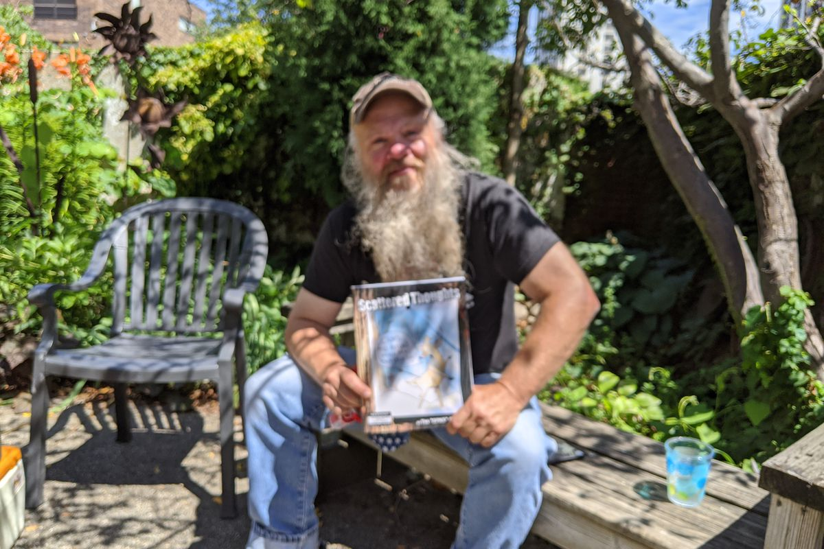 """Tim """"Spike"""" Davis poses with his just-released book of cartoons, """"Scattered Thoughts,"""" during an interview in a street-side garden in Uptown. Credit: Dale Bowman"""