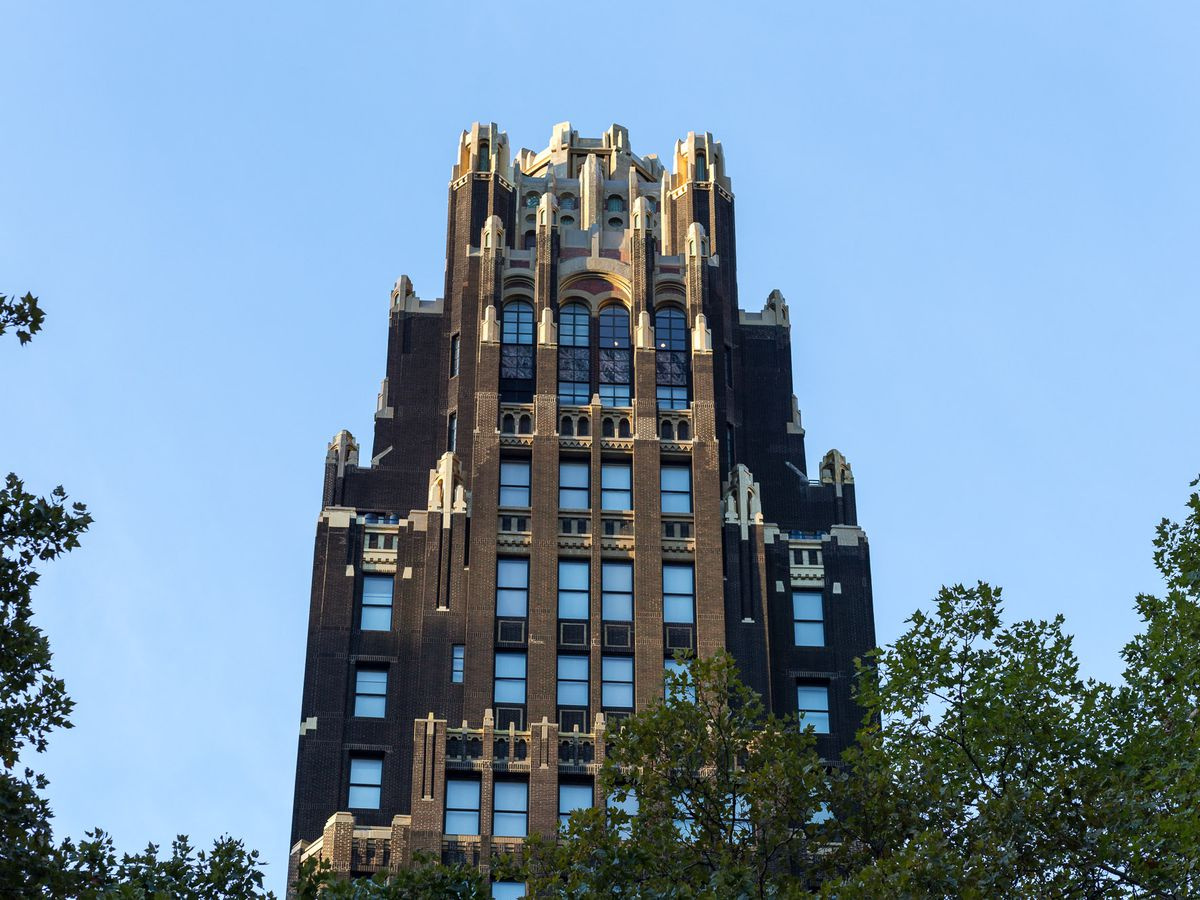 The top of a building with a dark brick facade and gold accents. There are setbacks on the building and large windows.