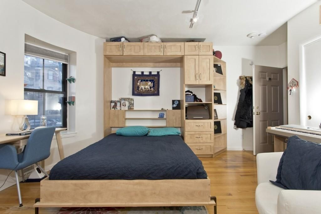A Murphy bed down from its walled installation and occupying much of the studio's living room.