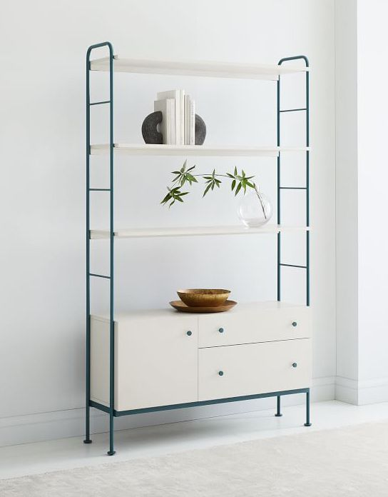 A three-tiered white bookshelf with drawers at the bottom and dark blue sides against a white wall. Four books are arranged on the top shelf while plants sit on the middle shelf, and wooden plates are stacked on the bottom shelf.