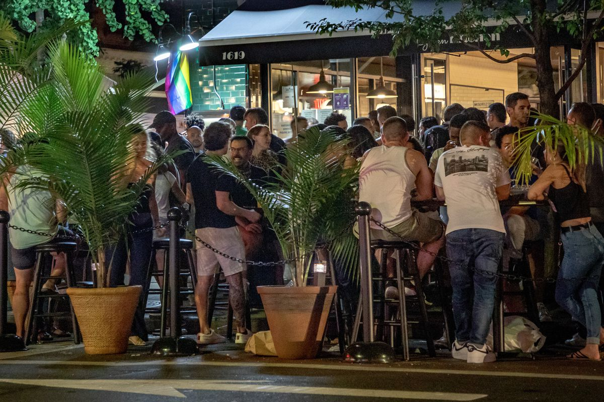 Revelers gather in an outdoor dining area roped off and separated from the street by potted plants