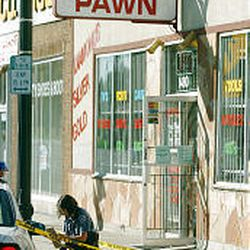 A Salt Lake police officer gathers evidence at Pappy's Pawn where a burglary suspect was shot by an officer before fleeing.