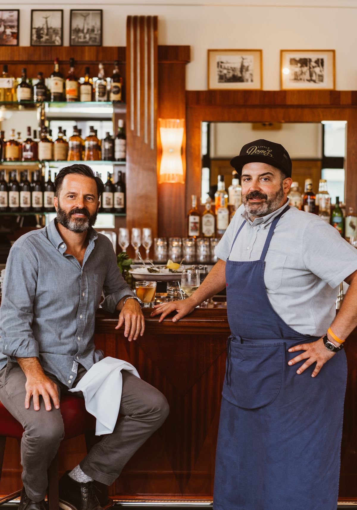 Two men lean on a new bar stool in front of their soon to open restaurant.