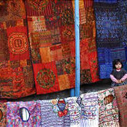 A tourist asks the price of a bedspread in Santiago Atitlan, Solola, west of Guatemala City. Guatemala is starting to shed its bloodstained reputation..