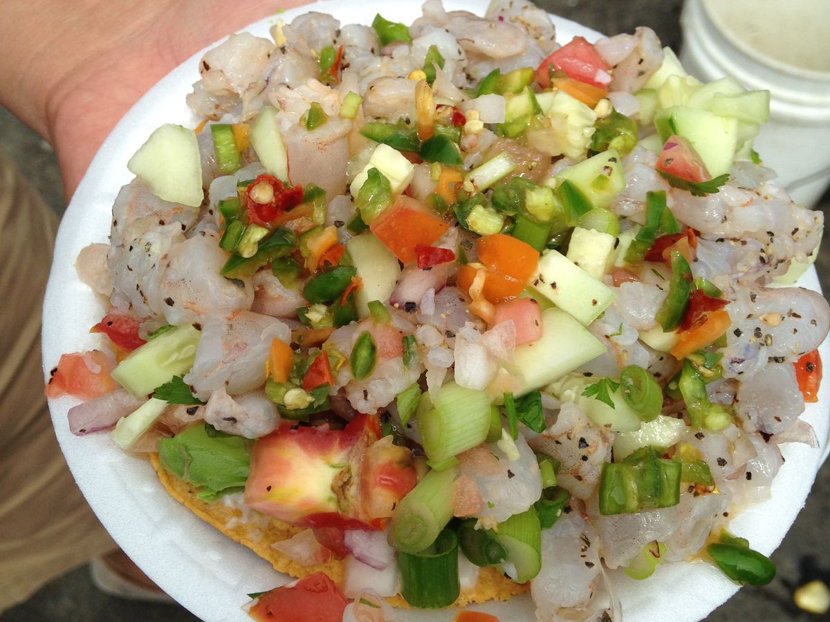 A tostada layered with shrimp, diced vegetables and other seafood
