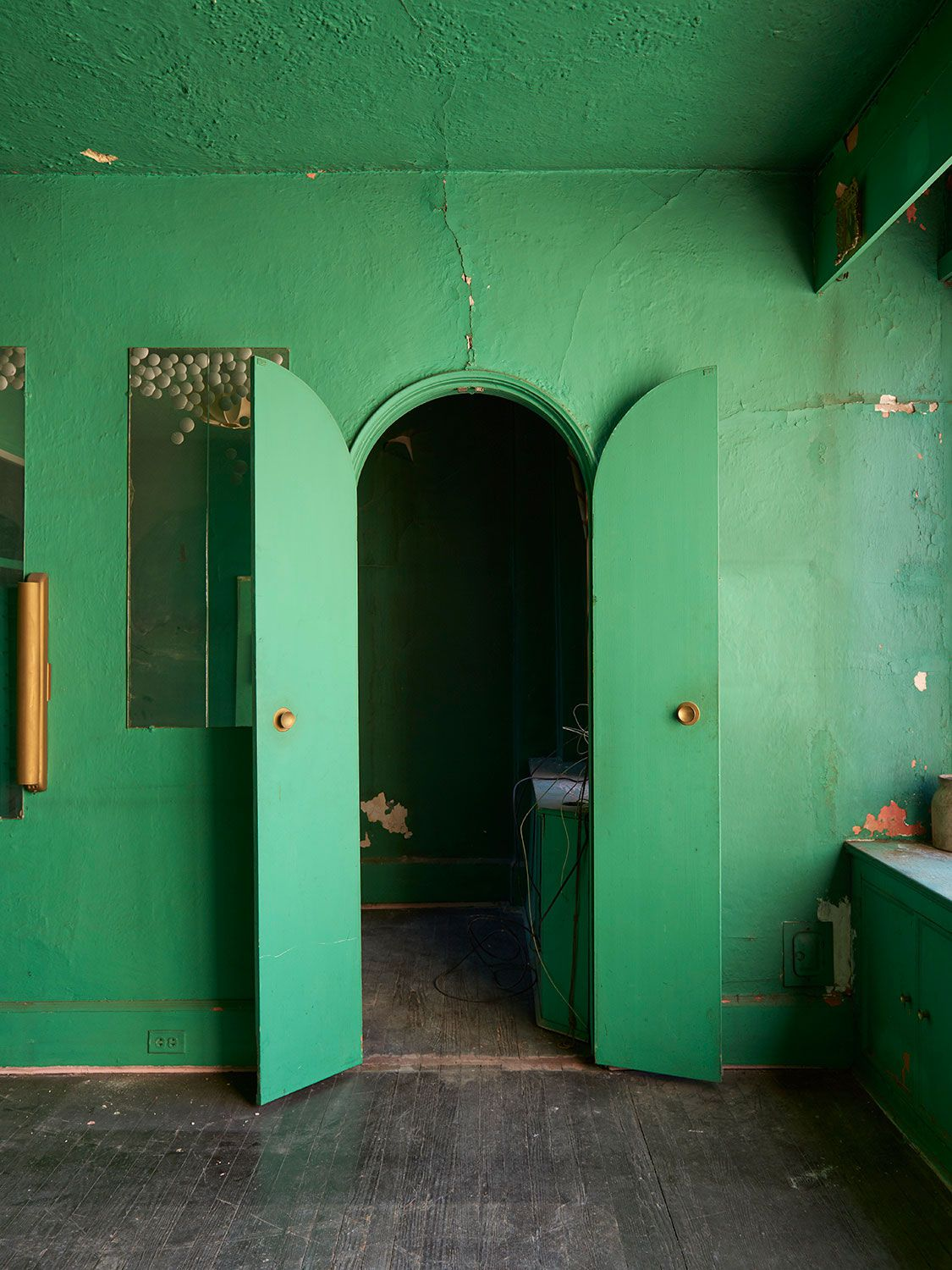 A room with hardwood floors with an arched doorway, all painted in bright green.