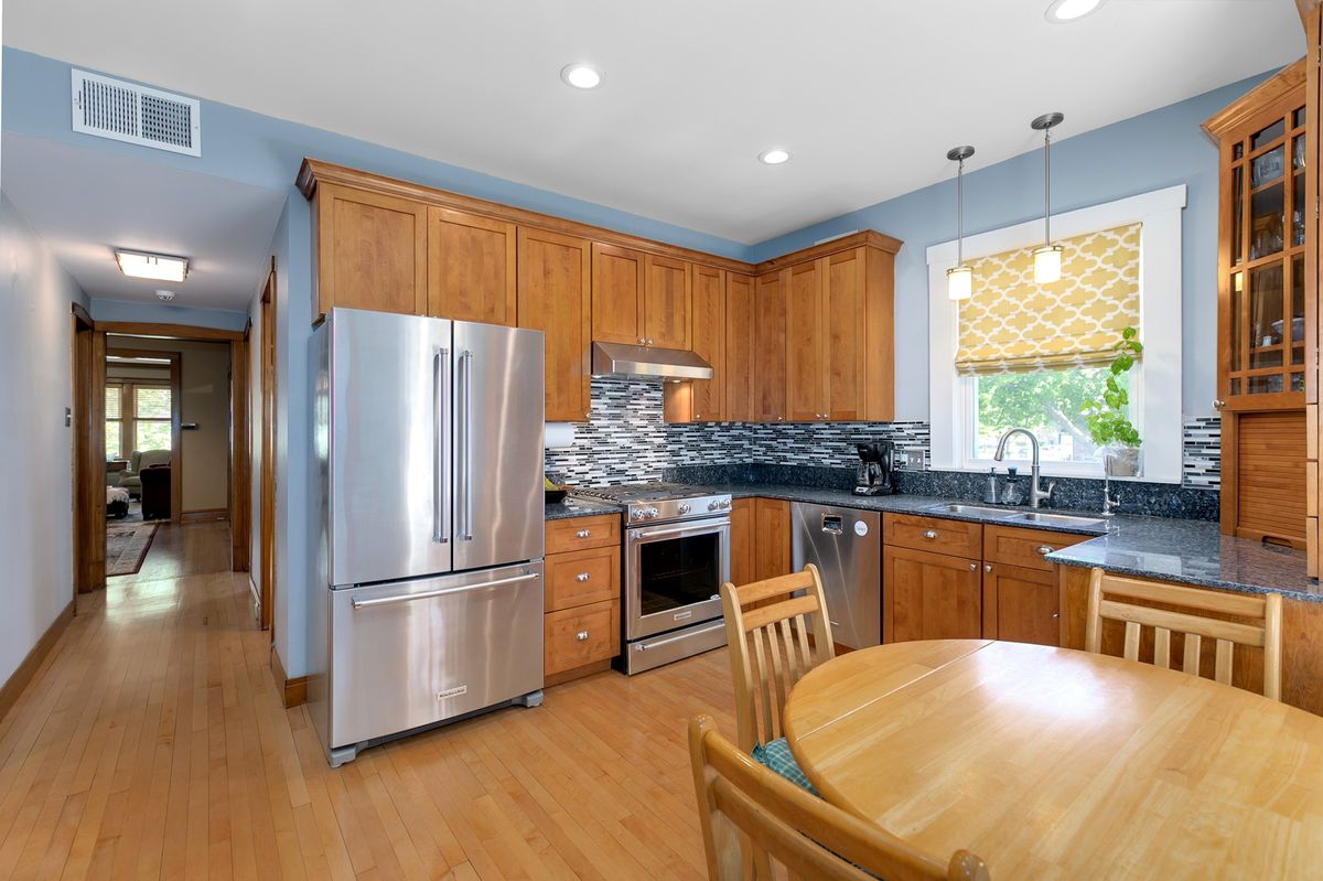 A kitchen with hardwood floors, matching cabinets, and steel appliances. There's also a circular wood table surrounded by three chairs.