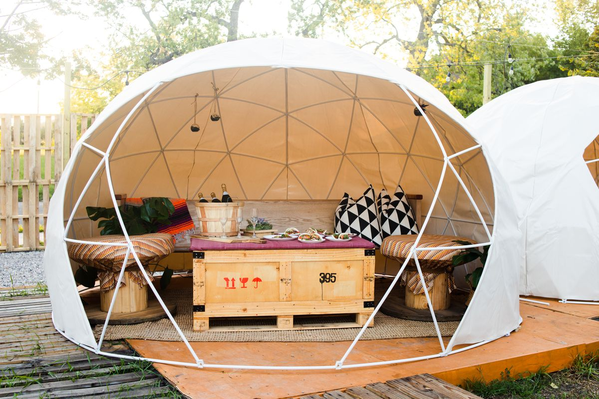 A geodesic dome is open to one side, revealing furniture in East Eats.
