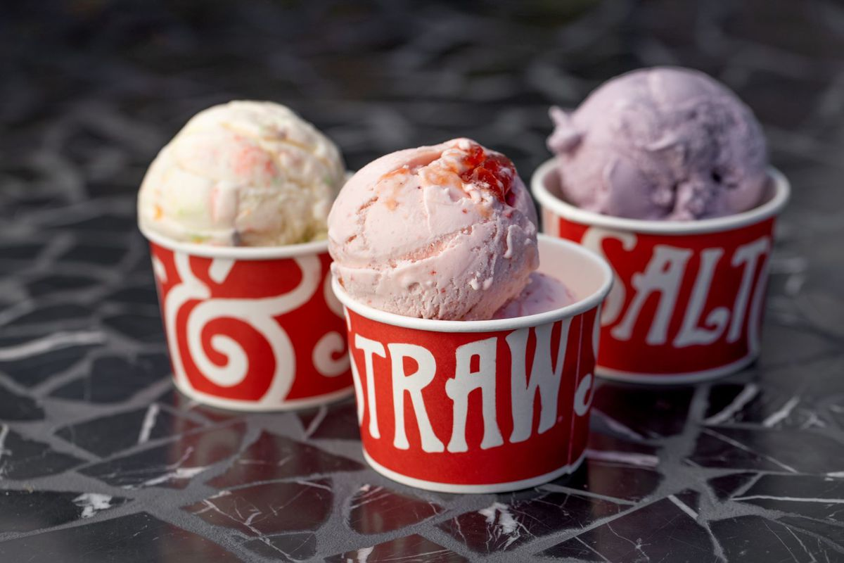 Three cups holding different flavors from Salt & Straw ice cream, with strawberry front and center