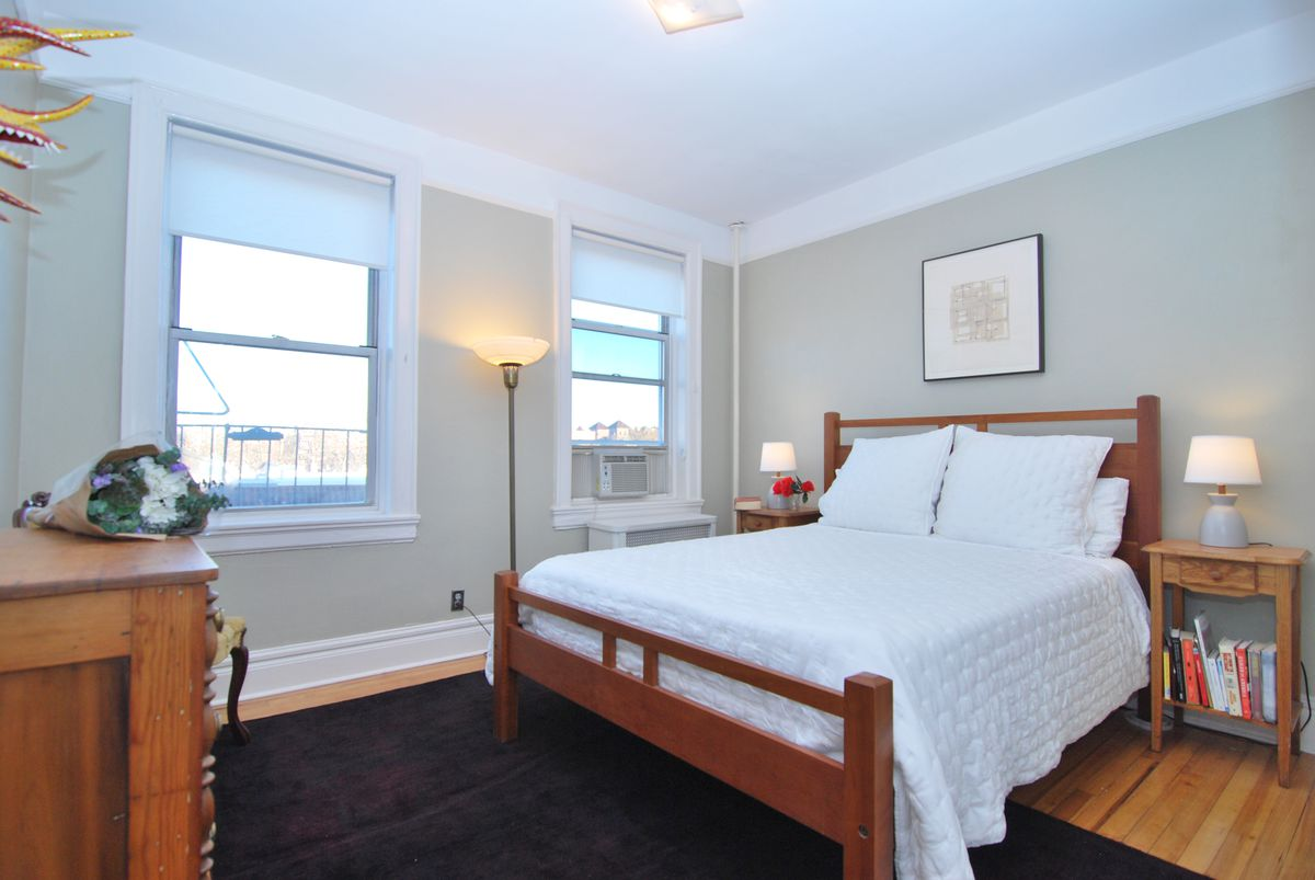 A bedroom with a medium-sized bed, hardwood floors, and two windows.