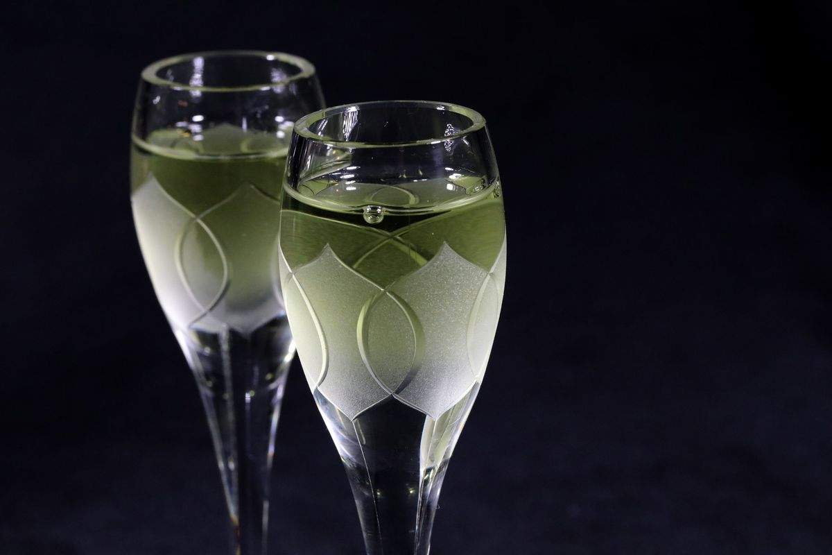 Two small glasses filled with Chartreuse on a black background