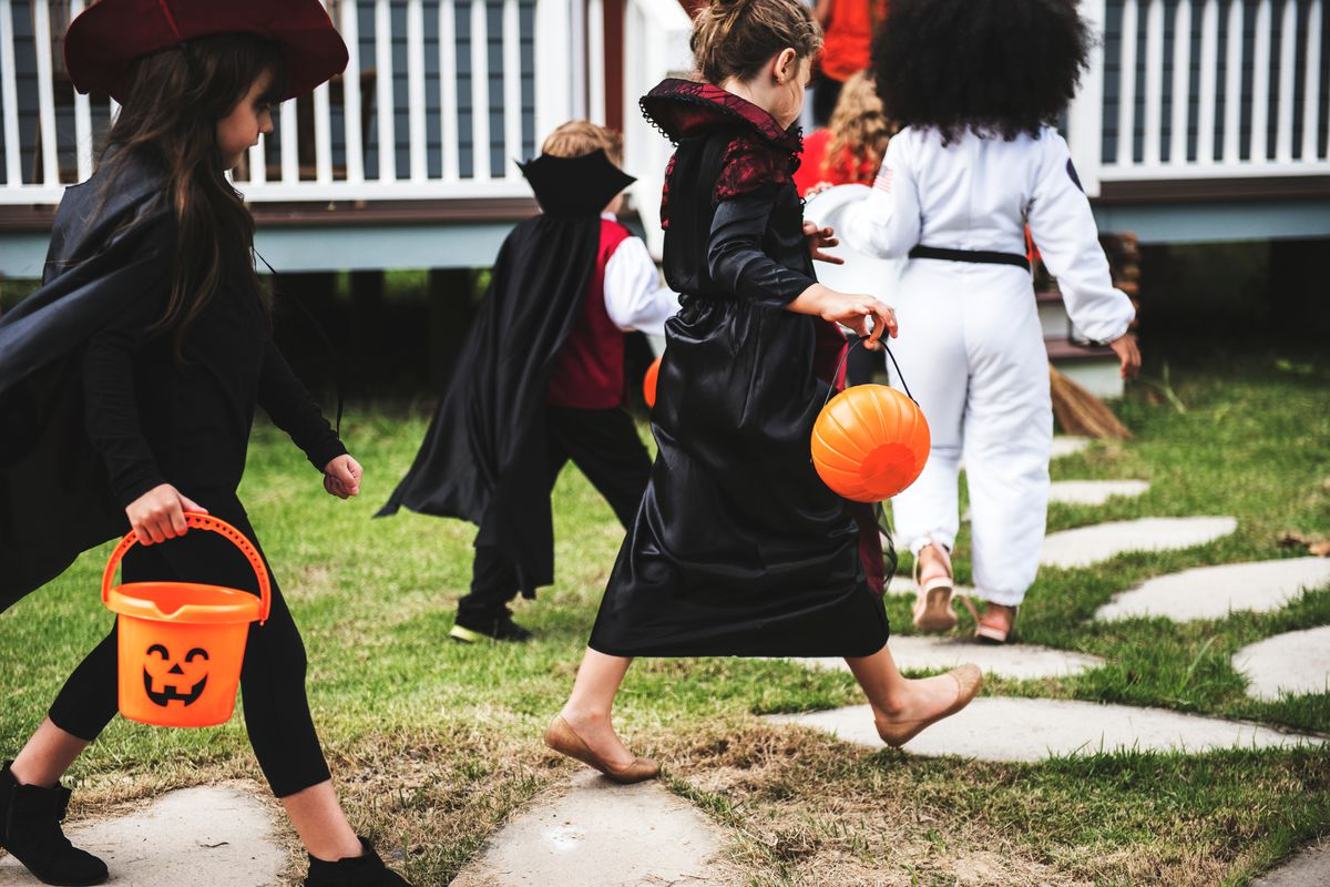 A group of kids in Halloween costumes approaches the door of a home, trick-or-treat buckets in hand
