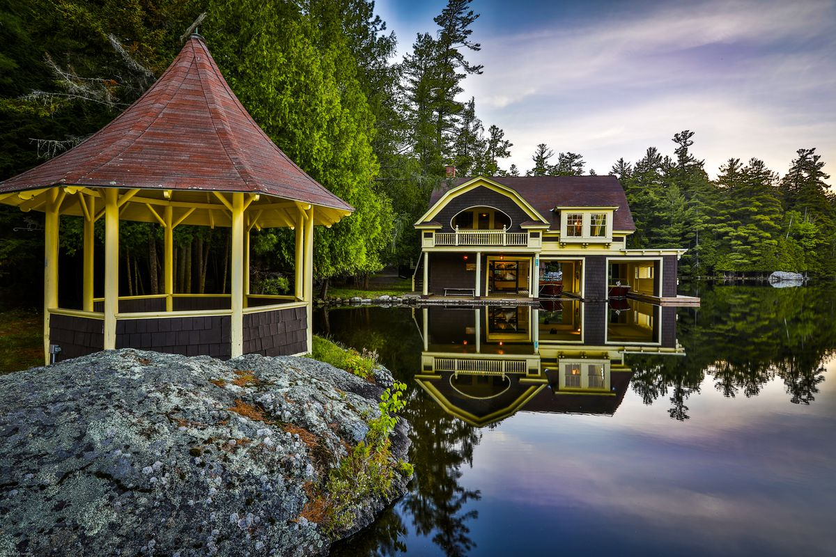 A yellow gazebo sits on a rock next to a lake with a large boathouse in the background.