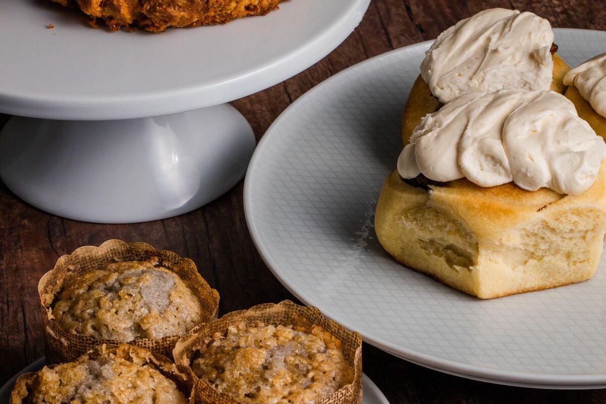A small plate and two cake stands with muffins, cream topped biscuits, and craggy scones.