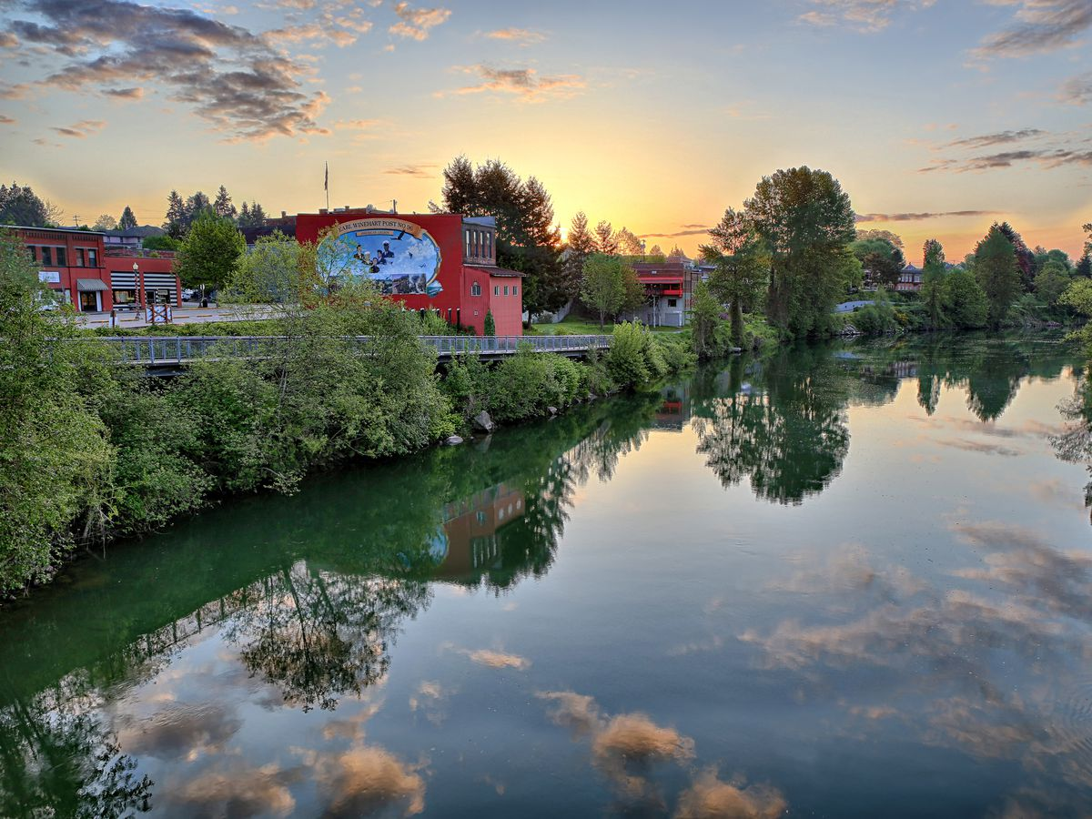 A wide stretch of river has blue sky, clouds, and surrounding trees reflected in it. On the left bank, there's a large, old red building, with more old buildings behind it.