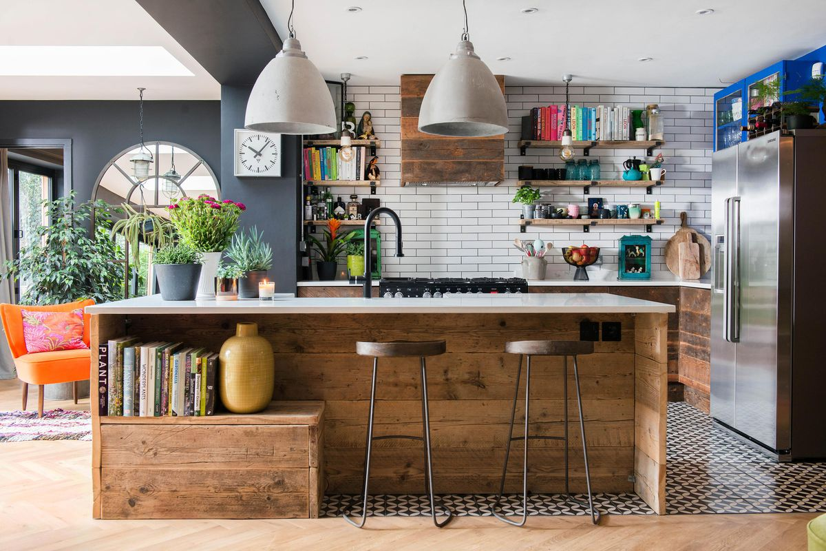 A modern kitchen with rustic wood accents. Books are stored in the kitchen island and on open shelving bringing a pop of color to the room.
