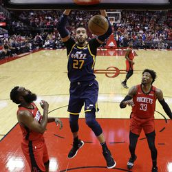 Utah Jazz center Rudy Gobert (27) dunks as Houston Rockets guard James Harden, left, forward Robert Covington (33) watch during the first half of an NBA basketball game, Sunday, Feb. 9, 2020, in Houston.