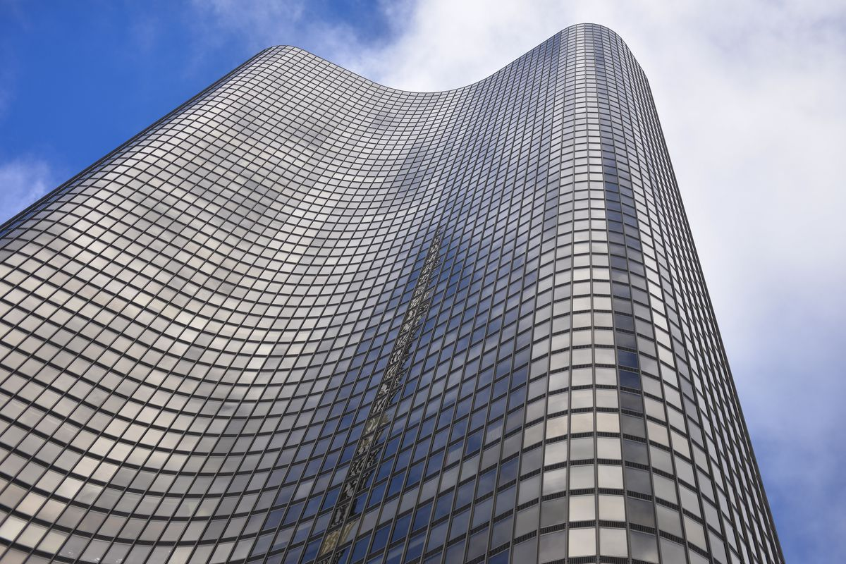 Looking up a a black, 70-story building with three curving lobes clad in a dark glass and aluminum facade.